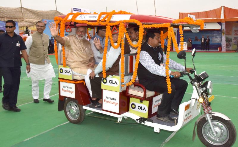 The Prime Minister, Shri Narendra Modi taking a ride on e-Rickshaw, on the launch of.