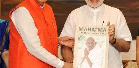 The Prime Minister, Shri Narendra Modi receiving a book 'Mahatma Gandhi's..