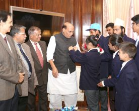 A group of children pinning flag on the Union Home Minister, Shri Rajnath Singh, as part of the Communal Harmony Campaign Week, in New Delhi